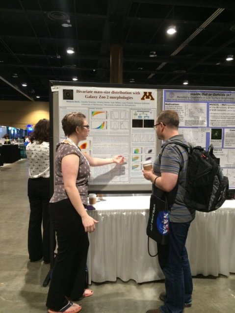 Melanie Beck discussing her poster with Prof. Chris Conselice (Univ. of Nottingham).